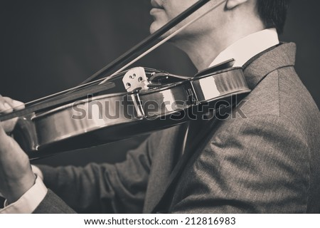 Asian male Musician plays Violin on Dark Background / B&W old film processed for vintage style photo - stock photo