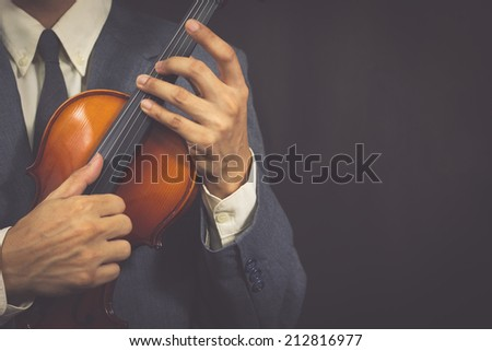 Asian male Musician plays Violin on Dark Background / old film & vintage photo style processed - stock photo
