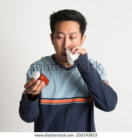 Asian male sneezing and holding medicine bottle, on plain background - stock photo