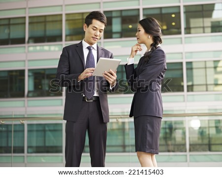 asian man and woman discussing business. - stock photo