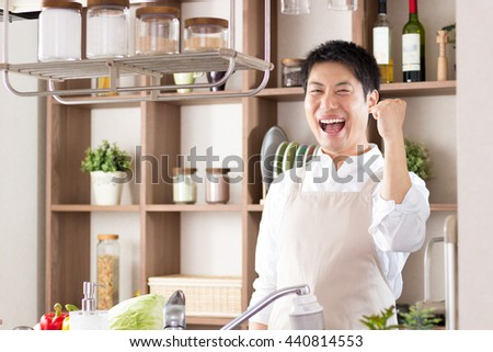 asian man cooking in the kitchen - stock photo