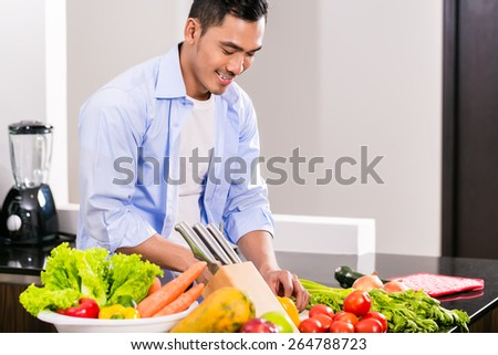 Asian man cutting vegetables and salad in kitchen - stock photo