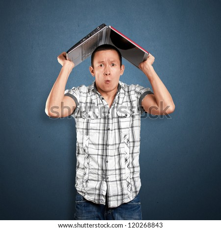 Asian man hides under the laptop in his hands - stock photo