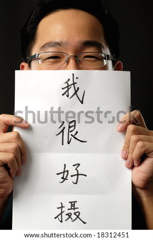 Asian man holding up a piece of paper that says he loves photography - stock photo