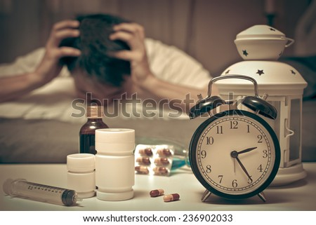 Asian Man in bed with tablets and drugs suffering insomnia, hangover and headache at night - stock photo