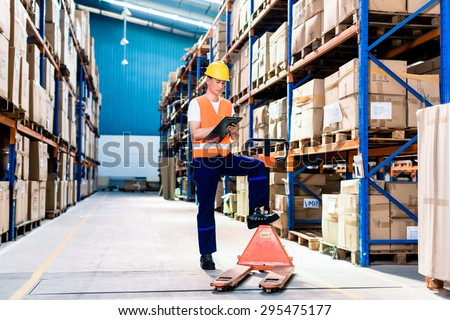 Asian man in industrial warehouse checking list - stock photo
