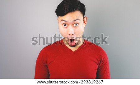 Asian man in red T-shirt is feelling surprised and shocked. - stock photo