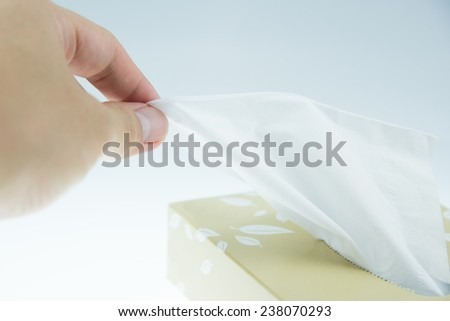 Asian man is taking tissue paper from the box - stock photo