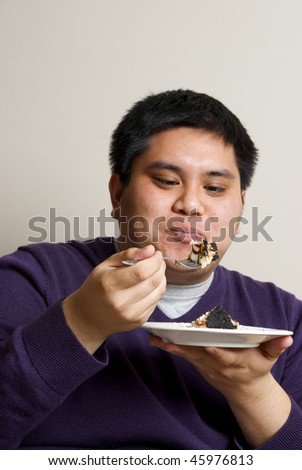 asian man looking at a big bite of dessert - stock photo