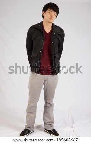 Asian man  looking at the camera with his hands behind his back and  a thoughtful expression - stock photo