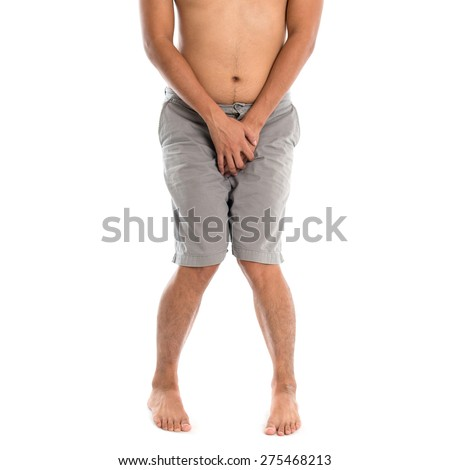 Asian man needing to urinate by covering his crotch with both hands, isolated on white background - stock photo
