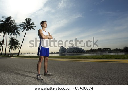 Asian man standing outside ready to exercise - stock photo