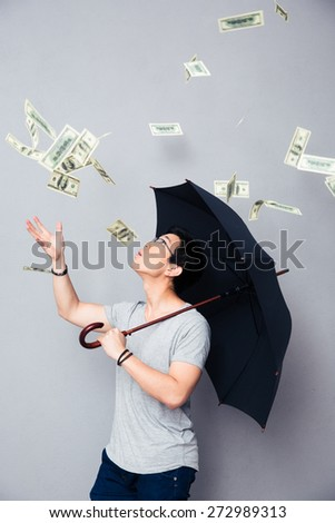 Asian man standing with umbrella in the rain of money over gray background - stock photo