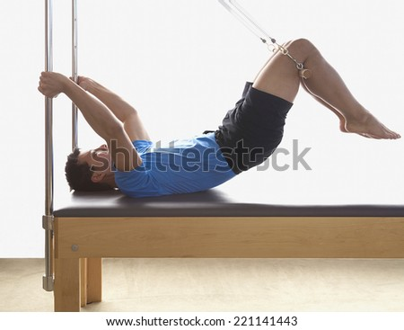 Asian man stretching on exercise equipment - stock photo
