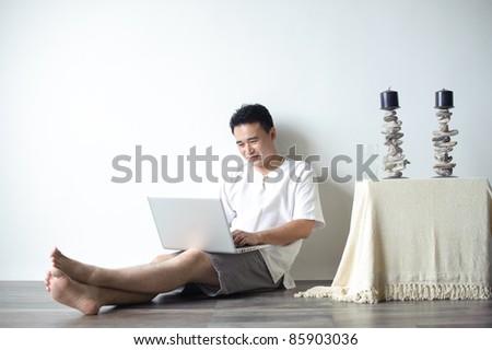 Asian Man Using Laptop Sitting on the floor - stock photo
