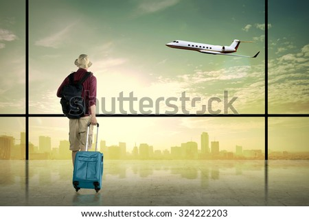 Asian man wearing hat carry suitcase. Business travel concept - stock photo