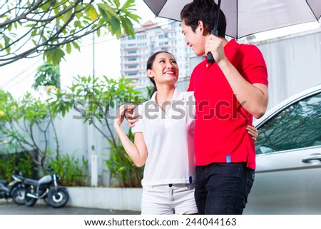 Asian man with umbrella walking woman in rain from car door to house - stock photo