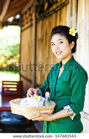 Asian masseuse inviting to salon - stock photo