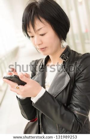 Asian mature woman use smart phone, closeup portrait. - stock photo
