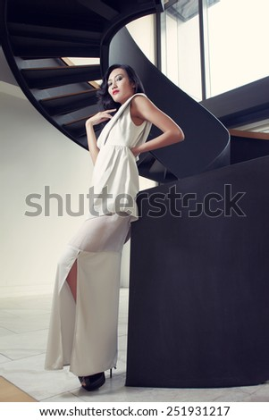 Asian model in white dress in interior with stair - stock photo