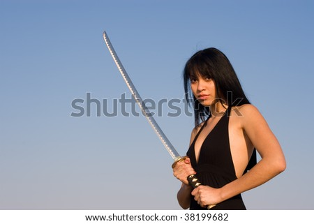 Asian model posing with a Samurai sword against blue sky - stock photo
