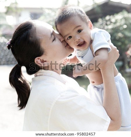 Asian mom kissing her son - stock photo