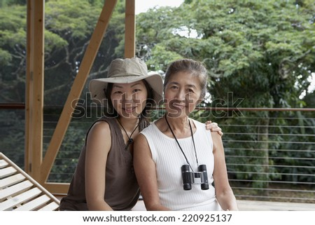 Asian mother and adult daughter hugging - stock photo