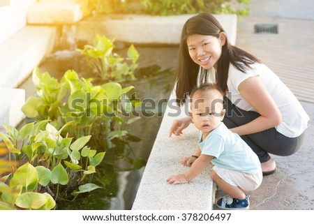 Asian mother and child having fun time at outdoor in sunset during vacations. - stock photo