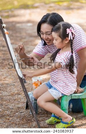 Asian mother and daughter enjoy painting in garden - stock photo