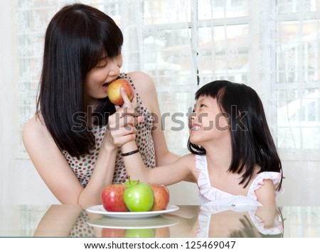 asian mother and daughter sharing an apple - stock photo