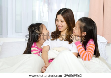 Asian mother and daughters bonding time on the bed - stock photo