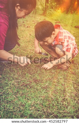 Asian mother and lovely son enjoying in nature. Young boy exploring nature at ground with magnifying glass. children playing outdoors with sunlight and happy family concept. - stock photo