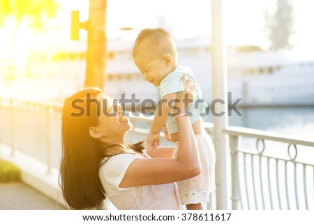 Asian mother and son having fun at outdoor in sunset during vacations. - stock photo
