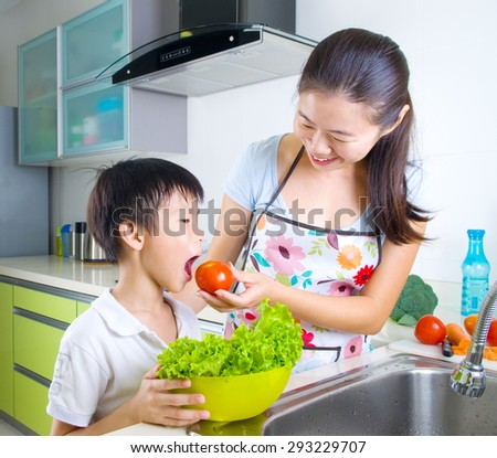 Asian mother and son in the kitchen - stock photo