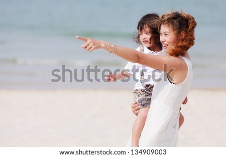 Asian mother and son on tropical beach - stock photo