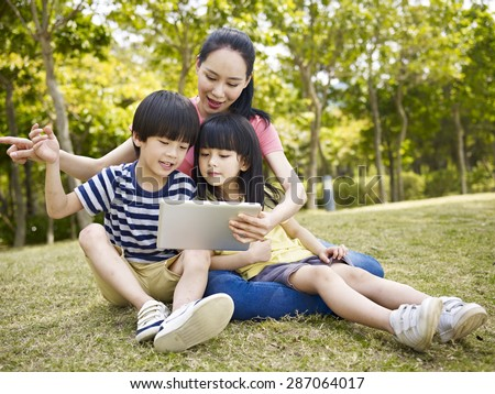 asian mother and two children using tablet computer outdoors. - stock photo