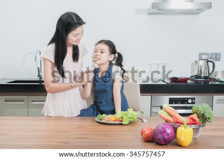 Asian mother feeding kid daughter vegetables in kitchen - stock photo
