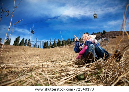 Asian mother hugging her baby and pointing at free space for text in the mountains. Ropeway with funicular and dramatic sky at the background - stock photo
