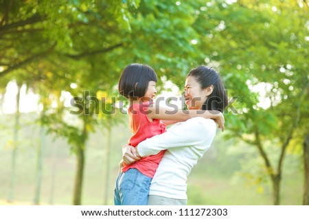 Asian mother hugging her daughter at outdoor park - stock photo
