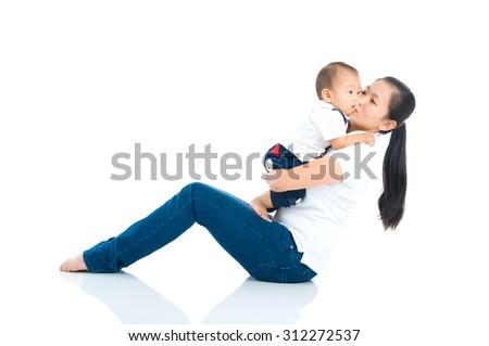 Asian mother kiss her baby - stock photo