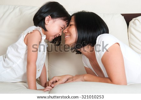 Asian mother playing with daughter on the sofa - stock photo