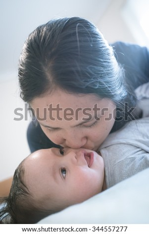 Asian mother plays with her mixed race newborn baby boy on a blue bed. Shallow depth of field, natural indoor bedroom setting, natural lighting, cool tones. - stock photo