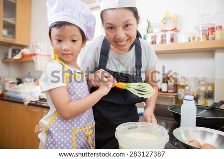 Asian mother teaching daughter making pancake - stock photo