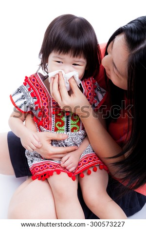 Asian mother wipes snot her daughter. Little girl with allergy symptom and sitting on young woman lap. On white background - stock photo