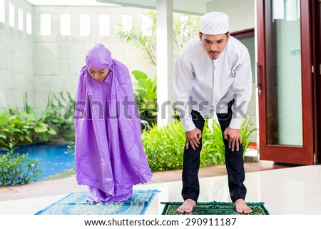 Asian Muslim couple, man and woman, praying at home sitting on prayer carpet in their house in front of the tropical garden - stock photo
