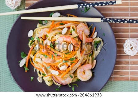 Asian noodles, pasta with shrimp, vegetables, carrots, peanuts, onions, Chinese dish - stock photo