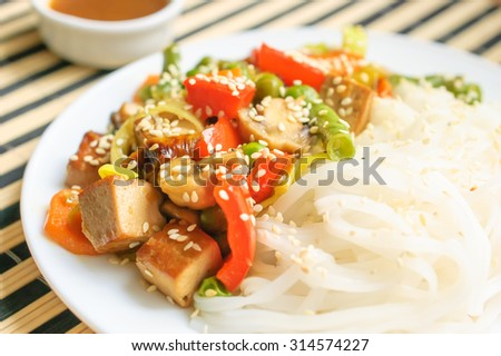 Asian noodles with tofu cheese, vegetables, sauce on a striped background with wooden sticks - stock photo