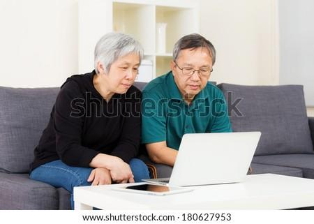 Asian old couple using laptop - stock photo