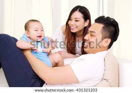 Asian parent and their six months old cheerful baby - stock photo