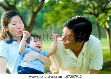 Asian parent having fun with their baby boy - stock photo